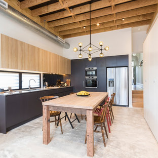 Photo of a mid-sized transitional l-shaped eat-in kitchen in Sydney with a double-bowl sink, light wood cabinets, quartz benchtops, stainless steel appliances, concrete floors and no island.