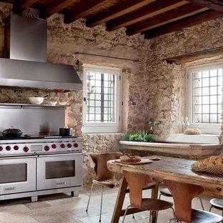 Diseño de cocina lineal, minimalista, de tamaño medio, cerrada, sin isla, con electrodomésticos de acero inoxidable, suelo de pizarra, fregadero integrado, salpicadero beige, salpicadero de azulejos de piedra y suelo beige