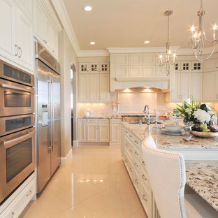 This is an example of a large traditional u-shaped open plan kitchen in Edmonton with beige splashback, stainless steel appliances, with island, an undermount sink, recessed-panel cabinets, white cabinets, granite benchtops, stone tile splashback and marble floors.