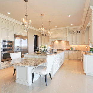 Photo of a large classic u-shaped open plan kitchen in Edmonton with a submerged sink, recessed-panel cabinets, white cabinets, granite worktops, beige splashback, stone tiled splashback, stainless steel appliances, marble flooring and an island.