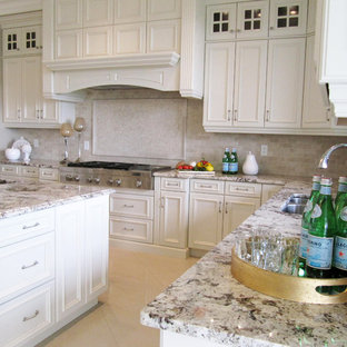 Large traditional u-shaped open plan kitchen in Edmonton with an undermount sink, recessed-panel cabinets, white cabinets, granite benchtops, beige splashback, stone tile splashback, stainless steel appliances, marble floors and with island.