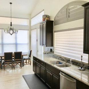 フェニックスの大きいエクレクティックスタイルのおしゃれなキッチン (ダブルシンク、レイズドパネル扉のキャビネット、濃色木目調キャビネット、御影石カウンター、グレーのキッチンパネル、セメントタイルのキッチンパネル、シルバーの調理設備、セメントタイルの床、グレーの床、マルチカラーのキッチンカウンター) の写真