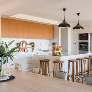 Contemporary l-shaped eat-in kitchen in Sydney with medium wood cabinets, white splashback, with island, white benchtop, flat-panel cabinets, subway tile splashback, stainless steel appliances, light hardwood floors and beige floor.