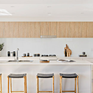 Contemporary galley kitchen in Wollongong with a drop-in sink, flat-panel cabinets, white cabinets, white splashback, glass sheet splashback, panelled appliances, with island, beige floor and white benchtop.