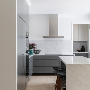 Inspiration for a mid-sized contemporary l-shaped kitchen in Sydney with flat-panel cabinets, grey cabinets, grey splashback, panelled appliances, porcelain floors, with island and beige floor.