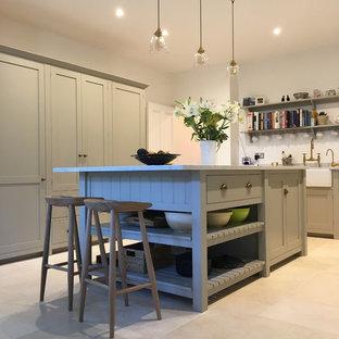サリーの中サイズのヴィクトリアン調のおしゃれなキッチン (エプロンフロントシンク、シェーカースタイル扉のキャビネット、グレーのキャビネット、大理石カウンター、白いキッチンパネル、セラミックタイルのキッチンパネル、シルバーの調理設備の、ライムストーンの床、ベージュの床) の写真