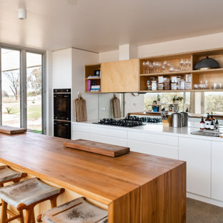 Design ideas for a mid-sized contemporary galley open plan kitchen in Other with a double-bowl sink, white cabinets, wood benchtops, metallic splashback, mirror splashback, white appliances, concrete floors, with island, grey floor, brown benchtop and flat-panel cabinets.