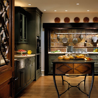 Design ideas for a large rustic l-shaped kitchen pantry in Chicago with a belfast sink, recessed-panel cabinets, green cabinets, limestone worktops, multi-coloured splashback, stone tiled splashback, integrated appliances, medium hardwood flooring and an island.