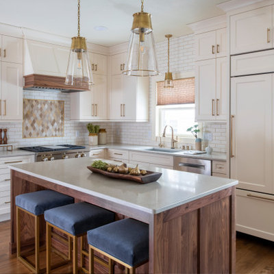 Mid-sized transitional l-shaped medium tone wood floor and brown floor eat-in kitchen photo in Minneapolis with an undermount sink, shaker cabinets, quartz countertops, an island, white cabinets, white backsplash, subway tile backsplash, stainless steel appliances and white countertops