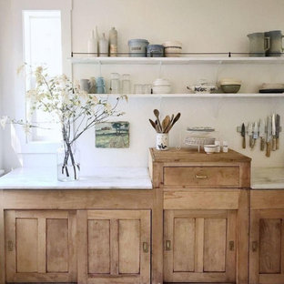 Small rustic eat-in kitchen designs - Example of a small mountain style single-wall medium tone wood floor and brown floor eat-in kitchen design in Columbus with a farmhouse sink, shaker cabinets, light wood cabinets, marble countertops, white backsplash, white appliances and white countertops