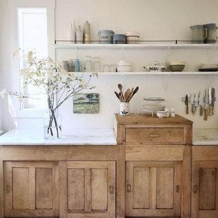 Diseño de cocina comedor lineal, rural, pequeña, con fregadero sobremueble, armarios estilo shaker, puertas de armario de madera clara, encimera de mármol, salpicadero blanco, electrodomésticos blancos, suelo de madera en tonos medios, suelo marrón y encimeras blancas