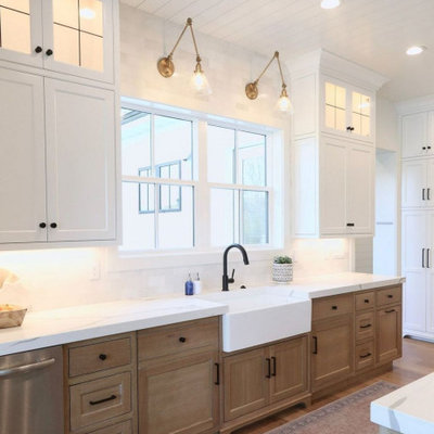 Kitchen - large contemporary l-shaped light wood floor and brown floor kitchen idea in Columbus with a farmhouse sink, shaker cabinets, light wood cabinets, quartz countertops, white backsplash, stone tile backsplash, stainless steel appliances, an island and white countertops