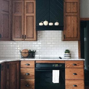 コロンバスの中サイズのトラディショナルスタイルのおしゃれなキッチン (アンダーカウンターシンク、レイズドパネル扉のキャビネット、中間色木目調キャビネット、クオーツストーンカウンター、白いキッチンパネル、サブウェイタイルのキッチンパネル、黒い調理設備、淡色無垢フローリング、茶色い床、白いキッチンカウンター) の写真