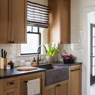 Immagine di una cucina contemporanea di medie dimensioni con lavello stile country, ante in stile shaker, ante in legno scuro, top in saponaria, paraspruzzi bianco, paraspruzzi con piastrelle diamantate, elettrodomestici bianchi, pavimento con piastrelle in ceramica, pavimento nero e top grigio