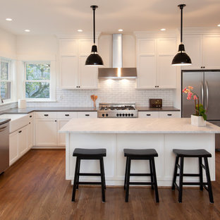 Traditional l-shaped kitchen in Sussex with a belfast sink, shaker cabinets, white cabinets, white splashback, metro tiled splashback, stainless steel appliances, medium hardwood flooring, an island, brown floors and grey worktops.