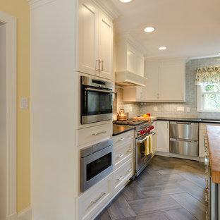 Klassische Küche mit Unterbauwaschbecken, Schrankfronten mit vertiefter Füllung, weißen Schränken, Küchenrückwand in Blau, Rückwand aus Metrofliesen, Küchengeräten aus Edelstahl, Porzellan-Bodenfliesen und Kücheninsel in Richmond