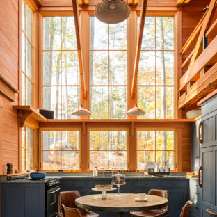 Mid-sized rustic eat-in kitchen designs - Mid-sized mountain style u-shaped brown floor and dark wood floor eat-in kitchen photo in Portland Maine with shaker cabinets, blue cabinets, soapstone countertops, paneled appliances, no island and window backsplash
