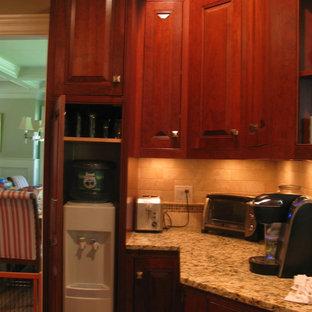 Mittelgroße Klassische Küche in L-Form mit Vorratsschrank, profilierten Schrankfronten, dunklen Holzschränken, Granit-Arbeitsplatte, Küchenrückwand in Beige, Rückwand aus Metrofliesen, Küchengeräten aus Edelstahl, hellem Holzboden und Kücheninsel in Boston