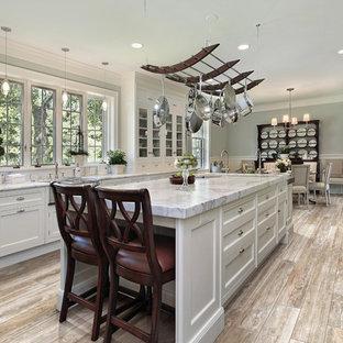 Modelo de cocina comedor de galera, tradicional renovada, con fregadero sobremueble, armarios con paneles con relieve, puertas de armario blancas y suelo de baldosas de porcelana