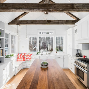 Mid-sized farmhouse eat-in kitchen pictures - Example of a mid-sized cottage l-shaped light wood floor eat-in kitchen design in New York with an undermount sink, white cabinets, quartz countertops, stainless steel appliances, an island, beaded inset cabinets and gray backsplash