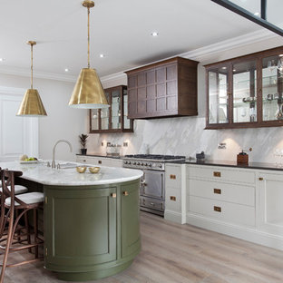 Transitional kitchen in West Midlands with a double-bowl sink, glass-front cabinets, dark wood cabinets, white splashback, marble splashback, stainless steel appliances, light hardwood floors, with island and beige floor.