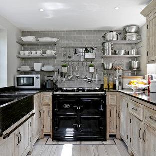 Photo of a small rural u-shaped kitchen in Hertfordshire with a belfast sink, shaker cabinets, distressed cabinets, grey splashback, metro tiled splashback, black appliances, light hardwood flooring, no island, beige floors and black worktops.