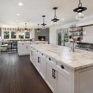 オレンジカウンティのカントリー風おしゃれなキッチン (エプロンフロントシンク、シェーカースタイル扉のキャビネット、白いキャビネット、クオーツストーンカウンター、白いキッチンパネル、サブウェイタイルのキッチンパネル、シルバーの調理設備の、濃色無垢フローリング、茶色い床) の写真