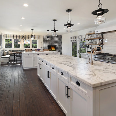 Inspiration for a cottage u-shaped dark wood floor and brown floor eat-in kitchen remodel in Orange County with a farmhouse sink, shaker cabinets, white cabinets, quartz countertops, white backsplash, subway tile backsplash, stainless steel appliances and two islands