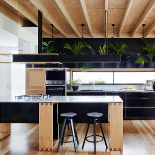 Inspiration for a small contemporary open plan kitchen in Melbourne with black cabinets, marble benchtops, white splashback, subway tile splashback, stainless steel appliances, light hardwood floors and with island.
