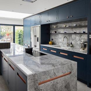 ロンドンの広いコンテンポラリースタイルのおしゃれなキッチン (ドロップインシンク、フラットパネル扉のキャビネット、青いキャビネット、御影石カウンター、グレーのキッチンパネル、大理石のキッチンパネル、シルバーの調理設備、セラミックタイルの床、グレーの床、グレーのキッチンカウンター) の写真
