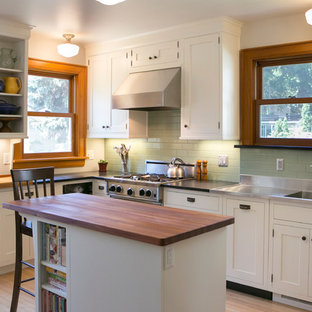 Inspiration for a mid-sized arts and crafts kitchen in Chicago with an integrated sink, shaker cabinets, white cabinets, zinc benchtops, green splashback, subway tile splashback, stainless steel appliances, light hardwood floors, with island and beige floor.