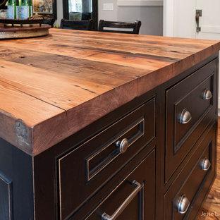 Rustik inredning av ett kök, med luckor med profilerade fronter, skåp i slitet trä, träbänkskiva, rostfria vitvaror, mellanmörkt trägolv och en köksö