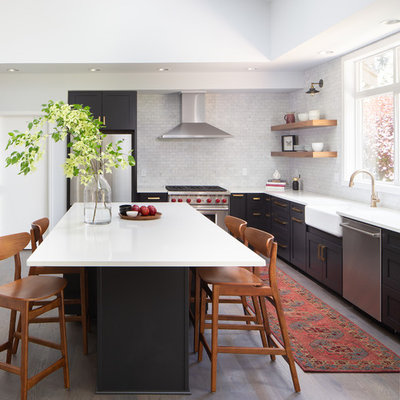 Inspiration for a transitional l-shaped medium tone wood floor and brown floor kitchen remodel in Seattle with a farmhouse sink, shaker cabinets, black cabinets, white backsplash, marble backsplash, stainless steel appliances, an island and white countertops