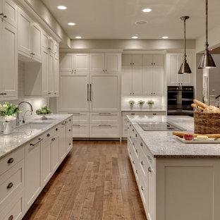 Пример оригинального дизайна: огромная кухня в стиле современная классика с врезной раковиной, фасадами в стиле шейкер, белым фартуком, техникой под мебельный фасад, гранитной столешницей, фартуком из стеклянной плитки, паркетным полом среднего тона, островом, белыми фасадами и серой столешницей