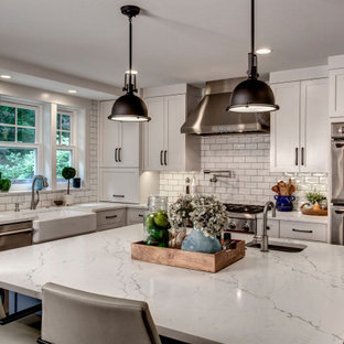 Transitional kitchen inspiration - Example of a transitional l-shaped kitchen design in Seattle with a farmhouse sink, shaker cabinets, white cabinets, white backsplash, subway tile backsplash, stainless steel appliances, an island and white countertops