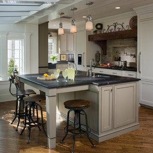 フィラデルフィアのインダストリアルスタイルのおしゃれなキッチン (アンダーカウンターシンク、シェーカースタイル扉のキャビネット、白いキャビネット、ベージュキッチンパネル、パネルと同色の調理設備) の写真
