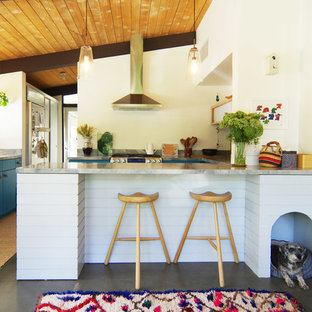 Mid-sized midcentury u-shaped kitchen in Los Angeles with flat-panel cabinets, blue cabinets, stainless steel appliances, concrete floors, a peninsula, marble benchtops, window splashback and grey floor.