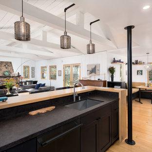 ロサンゼルスの中サイズのラスティックスタイルのおしゃれなキッチン (アンダーカウンターシンク、シェーカースタイル扉のキャビネット、黒いキャビネット、御影石カウンター、黒いキッチンパネル、石スラブのキッチンパネル、黒い調理設備、無垢フローリング、オレンジの床) の写真