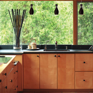 This is an example of a mid-sized midcentury u-shaped open plan kitchen in Chicago with an undermount sink, flat-panel cabinets, light wood cabinets, laminate benchtops, terra-cotta floors and no island.