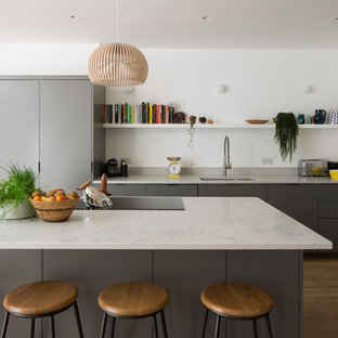 This is an example of a contemporary kitchen in London with flat-panel cabinets, grey cabinets, marble worktops, light hardwood flooring, an island, white worktops and a submerged sink.