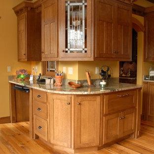 シカゴの大きいトラディショナルスタイルのおしゃれなキッチン (エプロンフロントシンク、シェーカースタイル扉のキャビネット、御影石カウンター、黄色いキッチンパネル、茶色い床、淡色木目調キャビネット、パネルと同色の調理設備、淡色無垢フローリング、ベージュのキッチンカウンター) の写真