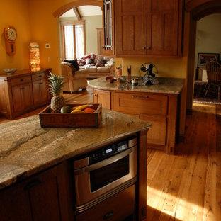 シカゴの大きいトラディショナルスタイルのおしゃれなキッチン (エプロンフロントシンク、御影石カウンター、シェーカースタイル扉のキャビネット、黄色いキッチンパネル、茶色い床、淡色木目調キャビネット、パネルと同色の調理設備、淡色無垢フローリング、ベージュのキッチンカウンター) の写真