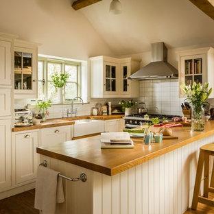 Photo of a medium sized rural u-shaped open plan kitchen in Wiltshire with a belfast sink, shaker cabinets, white cabinets, wood worktops, white splashback, ceramic splashback, black appliances, medium hardwood flooring and beige floors.