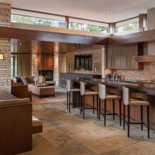 Zweizeilige Moderne Wohnküche mit flächenbündigen Schrankfronten, dunklen Holzschränken, Rückwand aus Steinfliesen, Kalkstein, Kücheninsel, Küchenrückwand in Braun, braunem Boden und brauner Arbeitsplatte in Houston