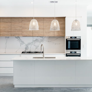 Inspiration for a contemporary galley kitchen in Perth with marble splashback, concrete floors, an undermount sink, flat-panel cabinets, white cabinets, white splashback, stainless steel appliances, with island, grey floor and white benchtop.