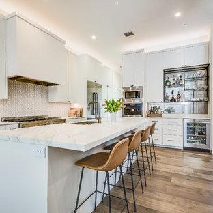 Foto de cocina costera con fregadero de un seno, armarios con paneles lisos, puertas de armario blancas, salpicadero blanco, electrodomésticos de acero inoxidable, una isla, encimeras blancas y suelo de madera clara