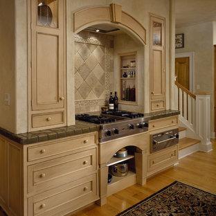 Inredning av ett klassiskt kök, med luckor med profilerade fronter, skåp i ljust trä, beige stänkskydd, stänkskydd i stenkakel, rostfria vitvaror och kaklad bänkskiva