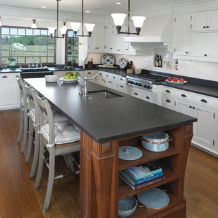 Inspiration for a large timeless medium tone wood floor kitchen remodel in Boston with a farmhouse sink, recessed-panel cabinets, distressed cabinets, granite countertops, white backsplash, ceramic backsplash, paneled appliances and an island