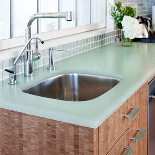 Design ideas for a small beach style l-shaped eat-in kitchen in Boston with an undermount sink, flat-panel cabinets, light wood cabinets, glass benchtops, green splashback, stainless steel appliances, light hardwood floors, no island, glass tile splashback and turquoise benchtop.