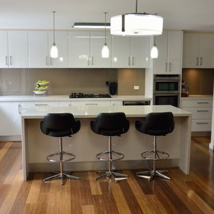 Large modern eat-in kitchen remodeling - Example of a large minimalist l-shaped bamboo floor eat-in kitchen design in Melbourne with a double-bowl sink, open cabinets, white cabinets, granite countertops, brown backsplash, glass sheet backsplash, stainless steel appliances and an island